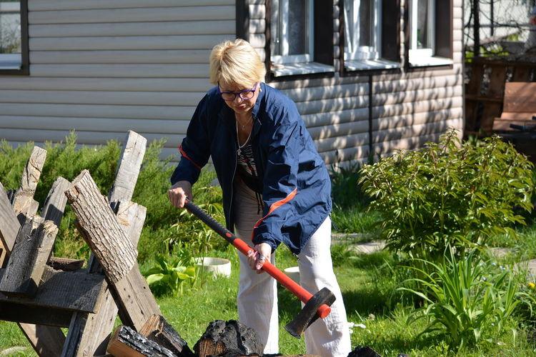 Woman cutting wood in back yard
