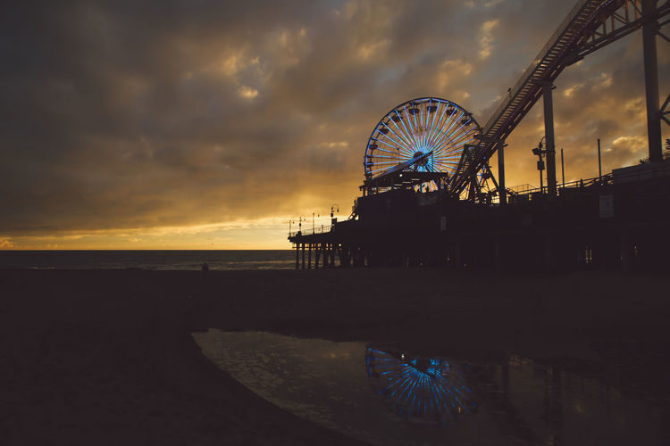 Santa Monica Pier At Beach Against Cloudy Sky During Sunset