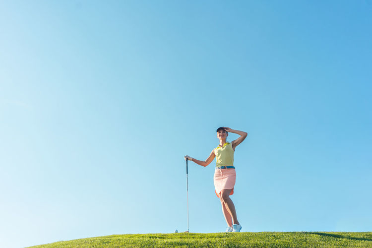 Beautiful woman on golf course Bautiful Woman Blue Copy Space Day Fit Fitness Full Length Golf Golf Club Golf Course Golfer Grass Leisure Activity Looking Low Angle View Outdoors Playing Sport