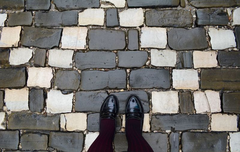 Low section of woman standing on paving stone