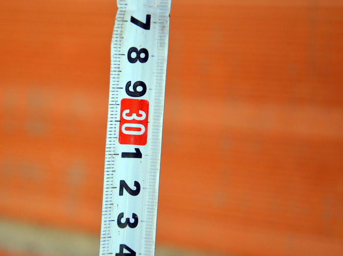 High angle close up of measuring tape against brick wall