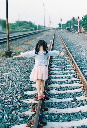 Full Length Rear View Of Girl Walking On Railroad Track