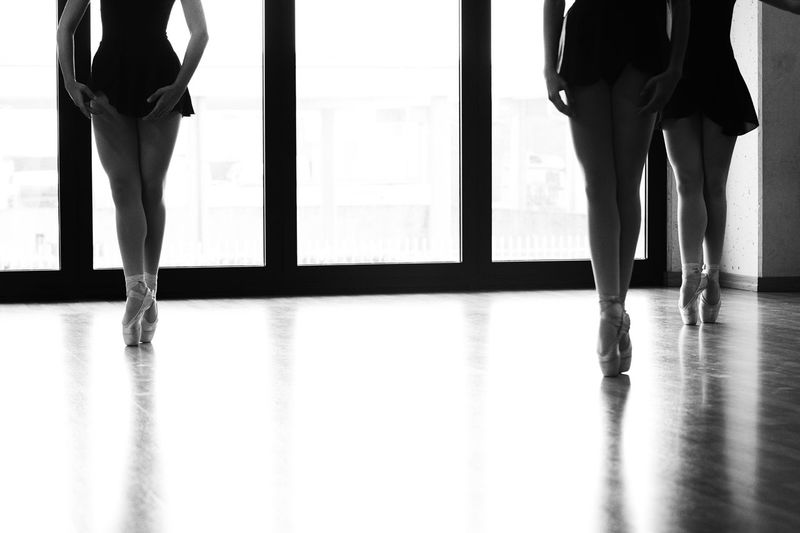 Low section of female ballerinas tiptoeing