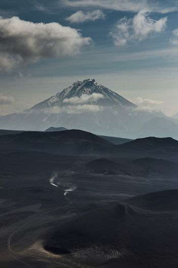Scenic view of volcanic landscape and mountain against cloudy sky