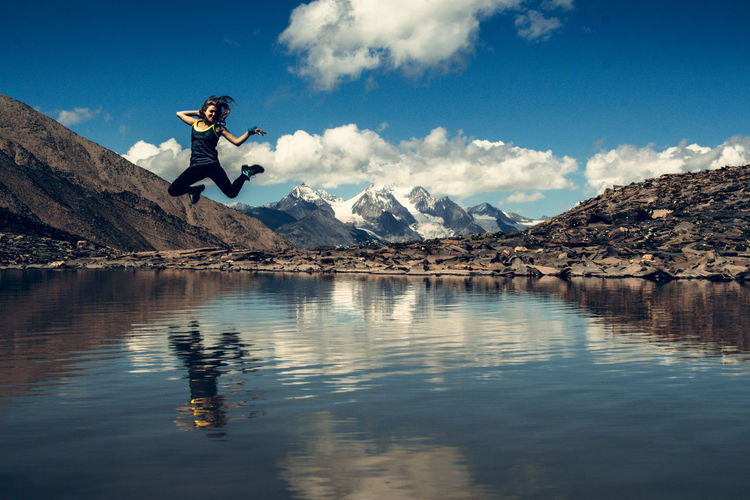 Woman jumping over lake against sky