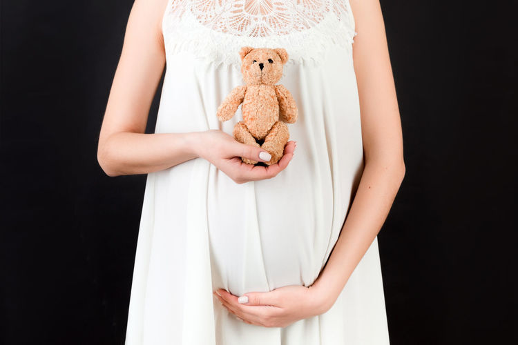 Midsection of a young woman holding toy against black background