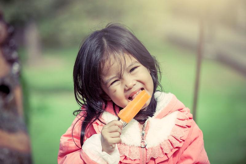 Portrait of cute girl licking ice cream