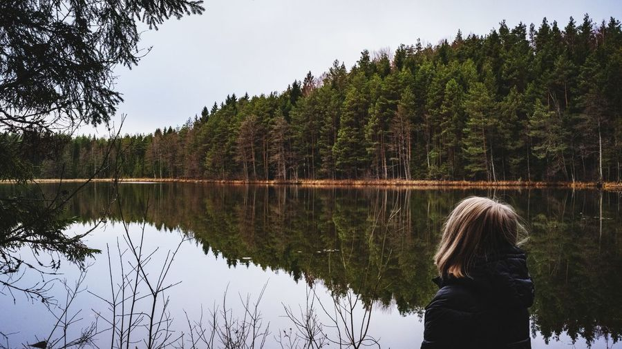 Rear View Of Woman Standing Against Lake In Forest