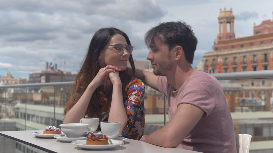 Young couple sitting at restaurant against city buildings