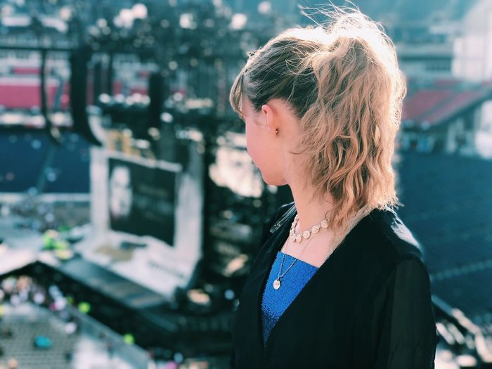 Close-up of young woman looking away in city