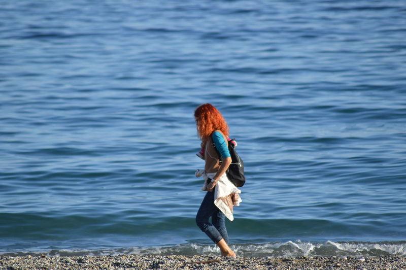 Woman standing at sea shore