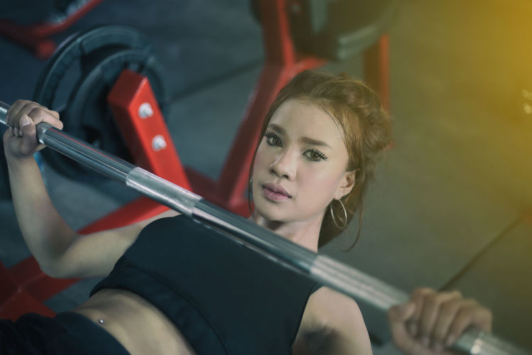 Portrait Of Smiling Young Woman Exercising In Gym
