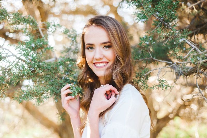 Portrait of smiling young woman by plant