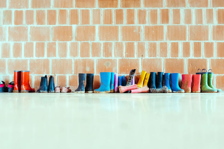 Multi colored chairs against brick wall