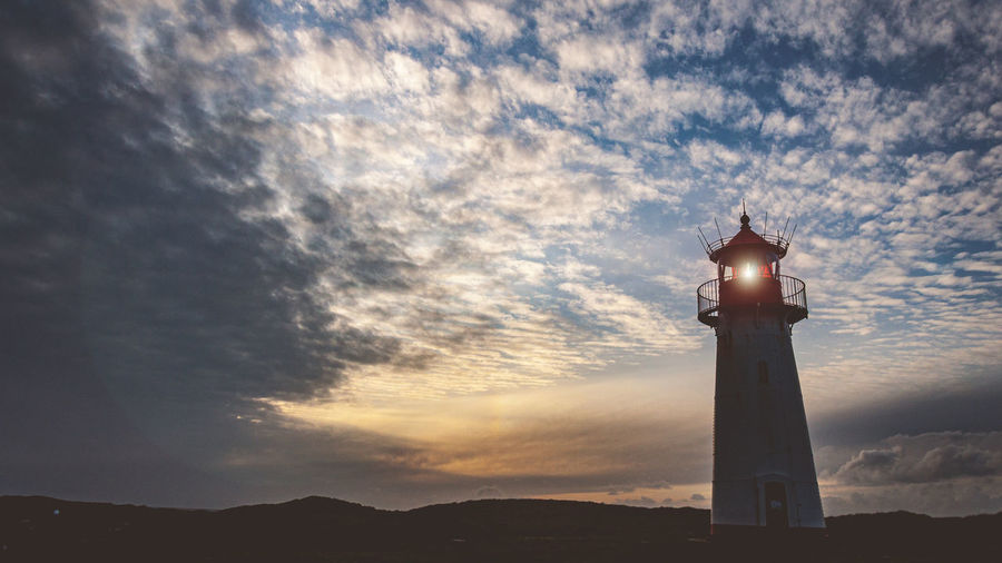 Low angle view of silhouette lighthouse against sky during sunset