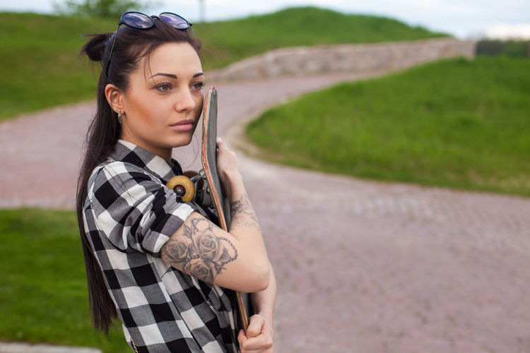 The woman with a tattoo is hugging her old skate on the background of park. Outdoors Young Women Holding Focus On Foreground Nature Road Hair Clothing Beautiful Woman Looking At Camera Hairstyle Adult Fashion Long Hair Women Standing Portrait Young Adult One Person Real People Lifestyles Leisure Activity Front View Casual Clothing Land