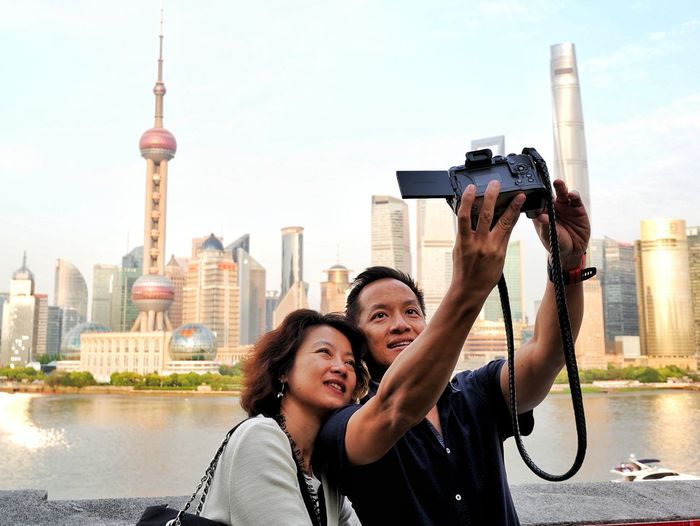 Mature couple taking selfie against skyscrapers