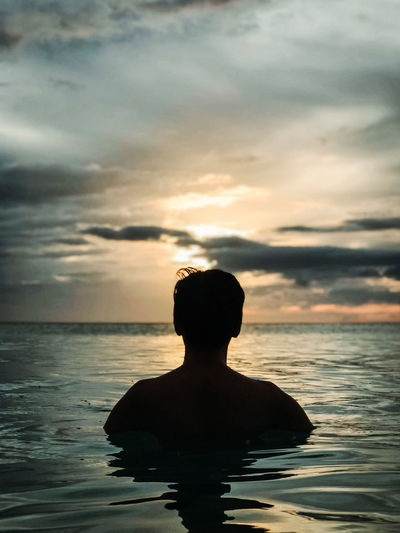 Rear view of silhouette man swimming in sea against sky at sunset