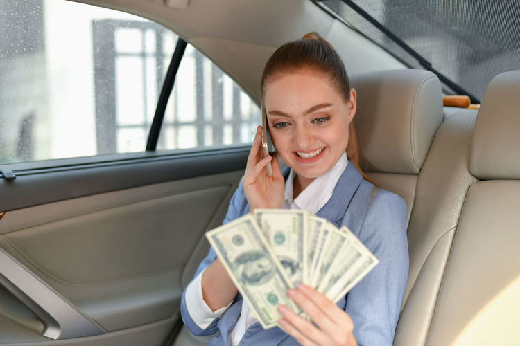 Smiling Businesswoman Holding Paper Currency While Sitting In Car