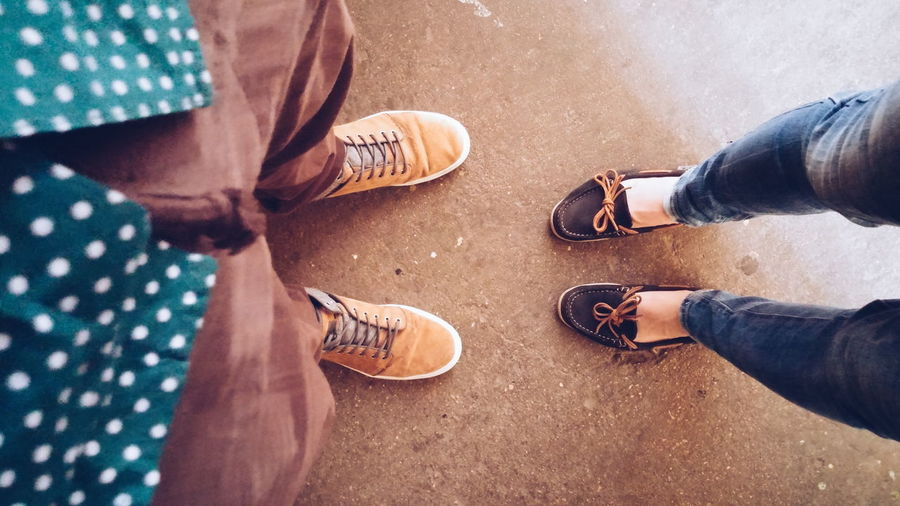 Low section of man and woman wearing shoes standing on street