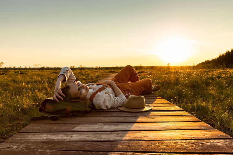 Woman lying on field against sky during sunset