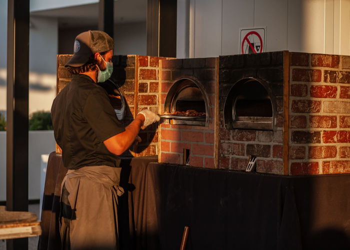 Man wearing mask preparing food at home