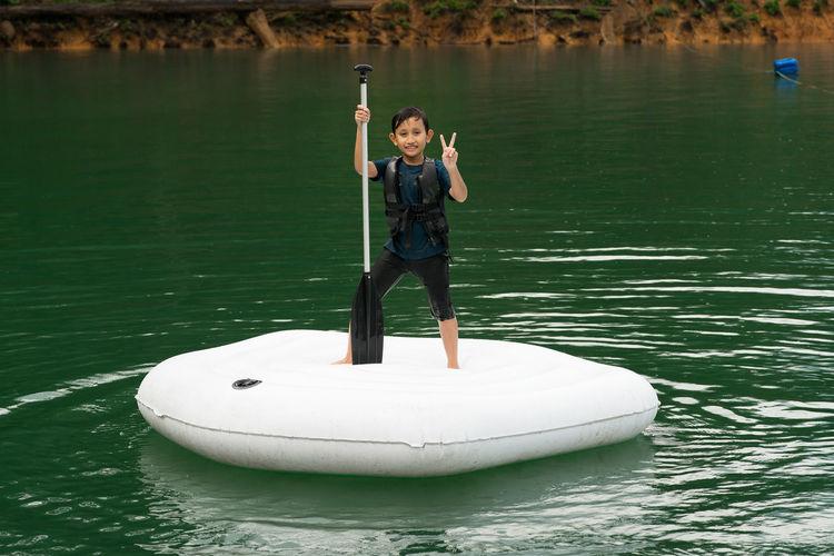 Man holding boat in lake