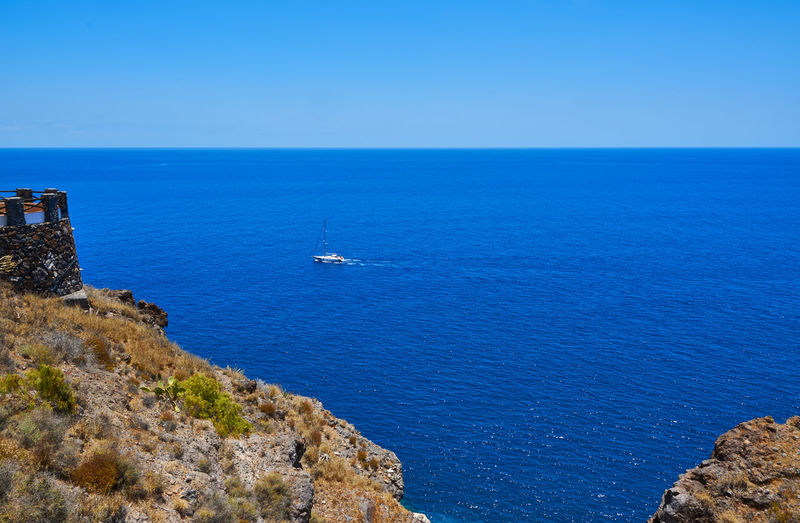 High Angle View Of Sailboat On Sea Against Clear Sky