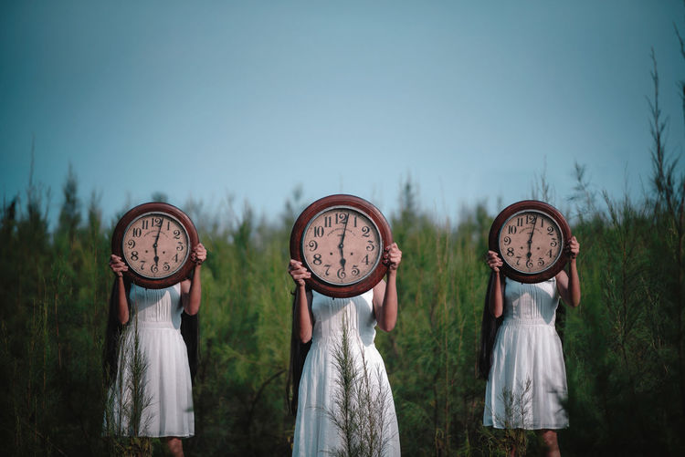 Women with wall clocks standing against plants