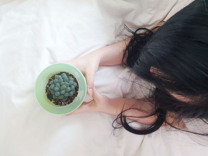 High angle view of girl holding bowl on bed
