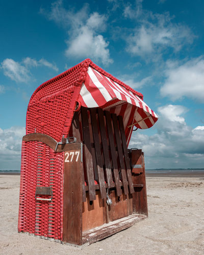 Hooded beach chairs against sky