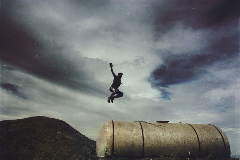 Man Jumping On Storage Tank By Mountain Against Sky
