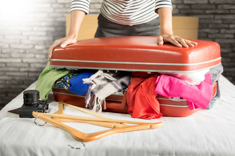 Midsection of woman packing clothes in suitcase on bed