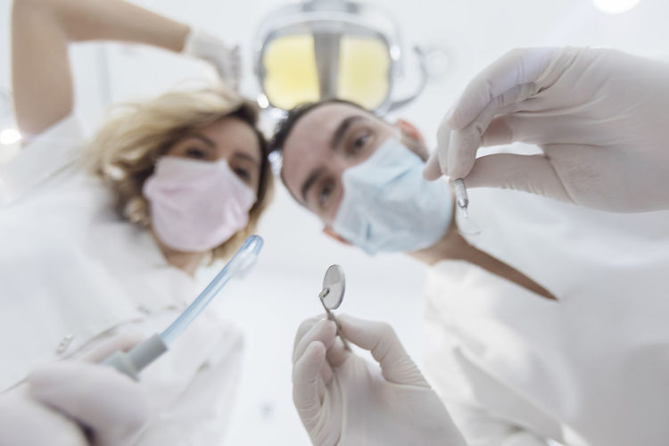 Low Angle Portrait Of Dentist With Nurse Holding Medical Equipment In Hospital