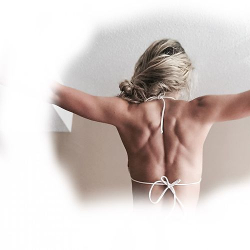 Rear view of shirtless woman against white background
