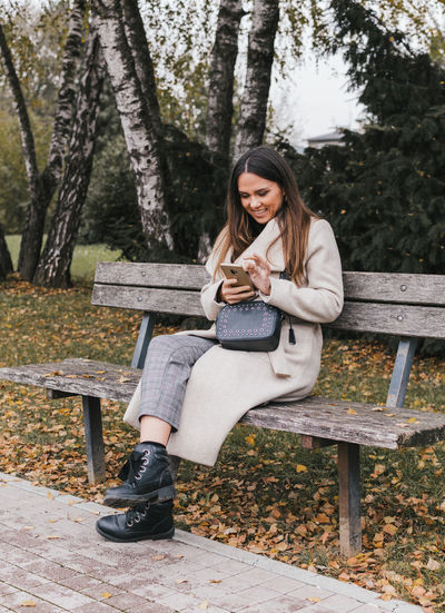 Full length of woman using phone while sitting on bench at park