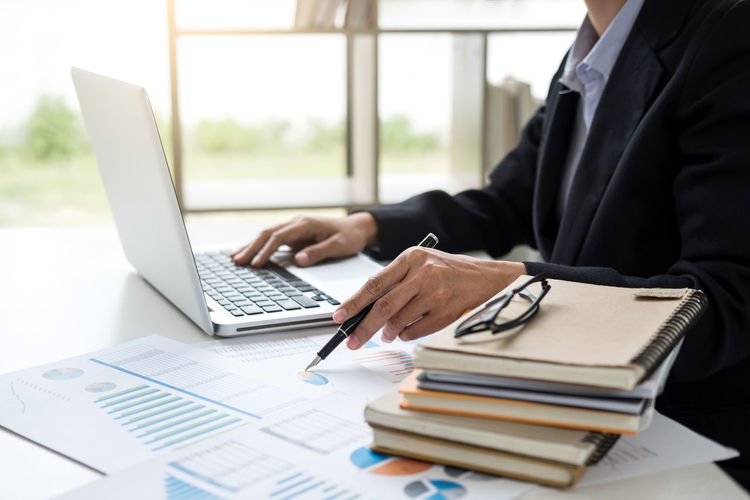 Midsection Of Businessman Using Laptop With Documents At Desk