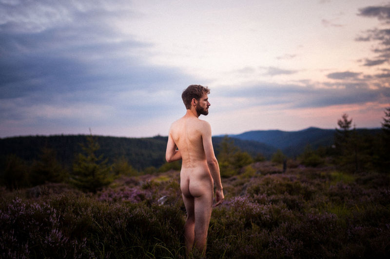 Rear view of naked man standing on field against sky