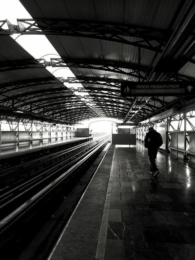 Rear view of woman at railroad station