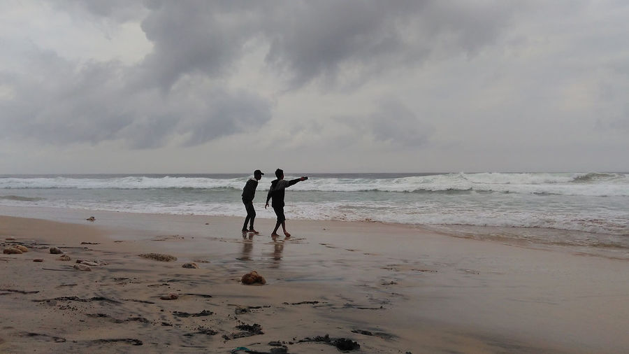 People standing at beach against cloudy sky