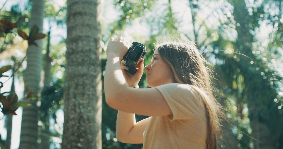 Woman photographing through smart phone outdoors