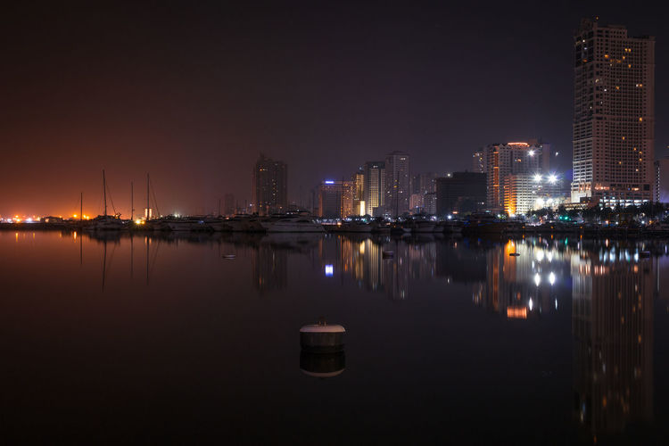 Reflection of illuminated city in water at night