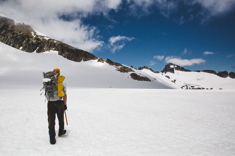 Winter Snow Mountain Cold Temperature Beauty In Nature Scenics - Nature Sky One Person Warm Clothing Standing Cloud - Sky Full Length Winter Sport Leisure Activity Clothing Mountain Range Nature Real People Lifestyles Snowcapped Mountain Outdoors