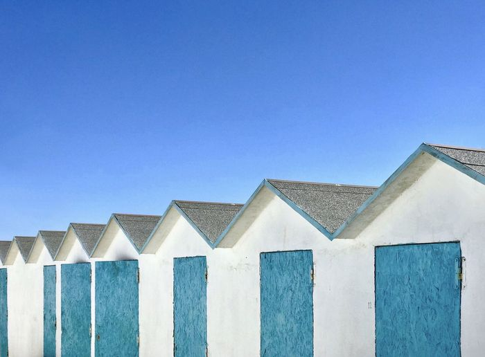Low angle view of beach houses against blue sky