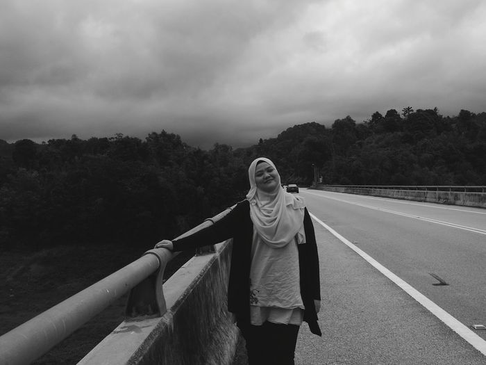 Young woman in hijab standing by railing on bridge against cloudy sky