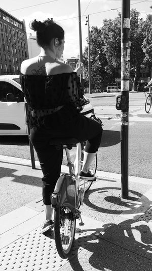 Rear view of woman riding bicycle on street