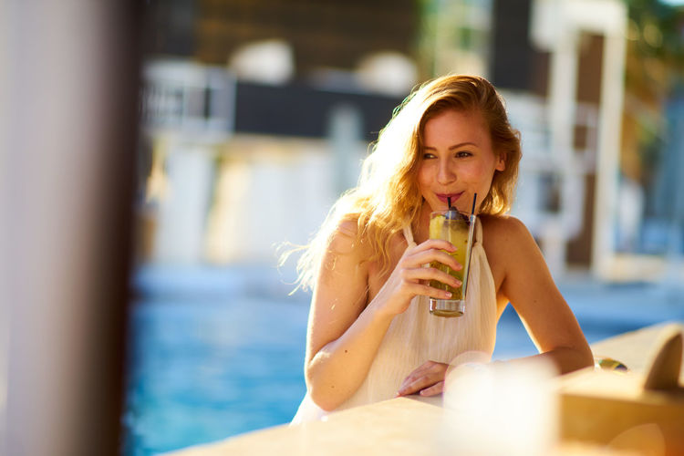 Woman drinking juice against swimming pool