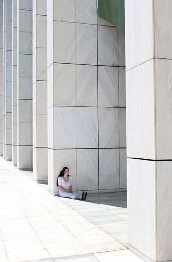 Depressed woman sitting by white column on sunny day