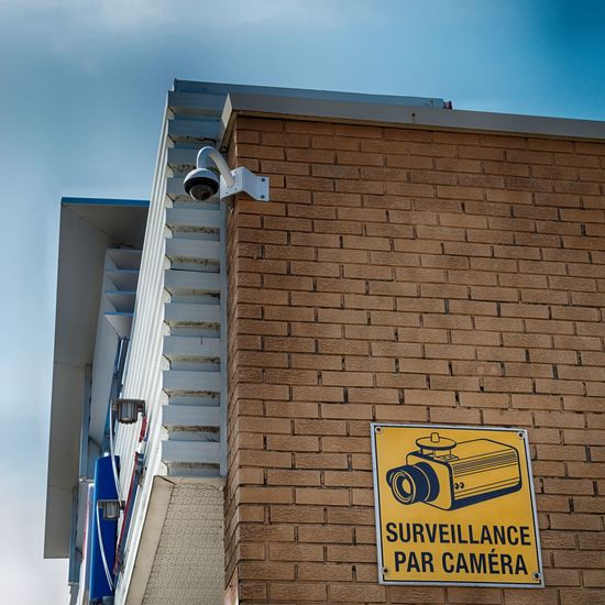 Architecture Big Brother Brick Wall Building Exterior Built Structure Camera Communication Day EyeEmNewHere Low Angle View Low Angle View No People Outdoors Privacy Sign Sky Surveillance Surveillance Camera Warning Warning Sign
