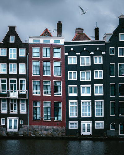 The unique houses of damrak on a cloudy day found in the heart of the dutch capital of amsterdam.